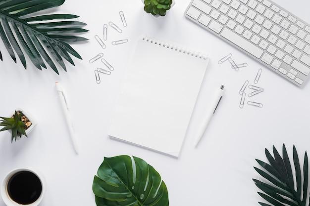 Bloc de notas espiral en blanco con teclado; clips de papel y hojas verdes sobre fondo blanco