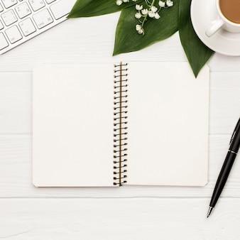 Bloc de notas de espiral en blanco con teclado, taza de café y pluma sobre fondo blanco