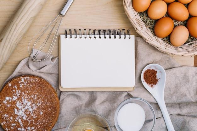 Bloc de notas espiral en blanco con varios ingredientes para hornear pastel en mesa