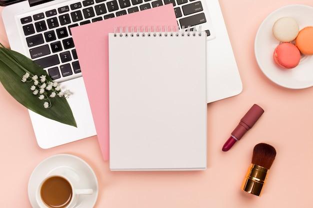 Bloc de notas de espiral en la computadora portátil con macarrones y taza de café con pinceles de maquillaje sobre fondo coloreado