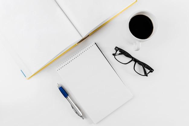 Bloc de notas en espiral; gafas; vaso; pluma y libro sobre fondo blanco