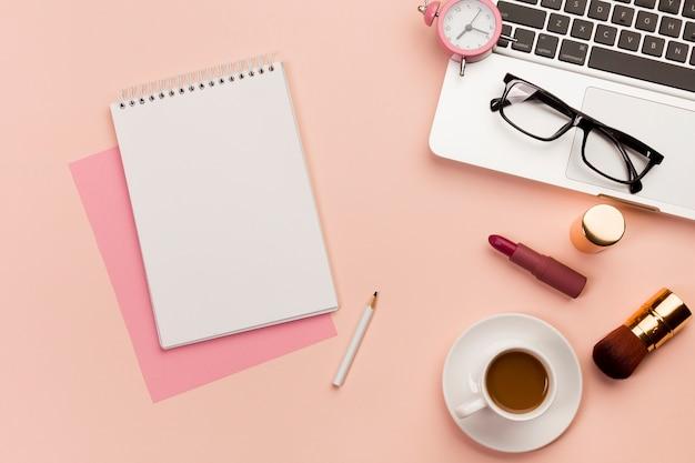 Bloc de notas en espiral con laptop, lentes, laptop, producto de maquillaje y taza de café sobre fondo coloreado