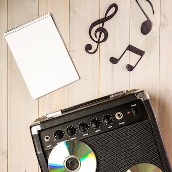 Bloc de notas en espiral; nota musical y amplificador con disco compacto en escritorio de madera.