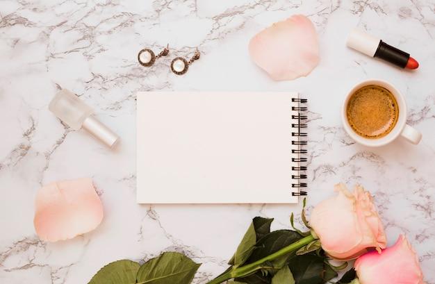 Bloc de notas espiral con pendientes en blanco; botella de barniz de uñas; lápiz labial; rosas y taza de café sobre fondo de mármol.