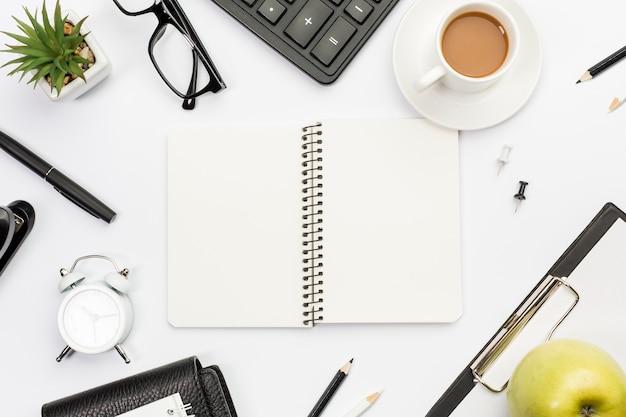 Bloc de notas en espiral rodeado de papelería, manzana y café en el escritorio de oficina blanco