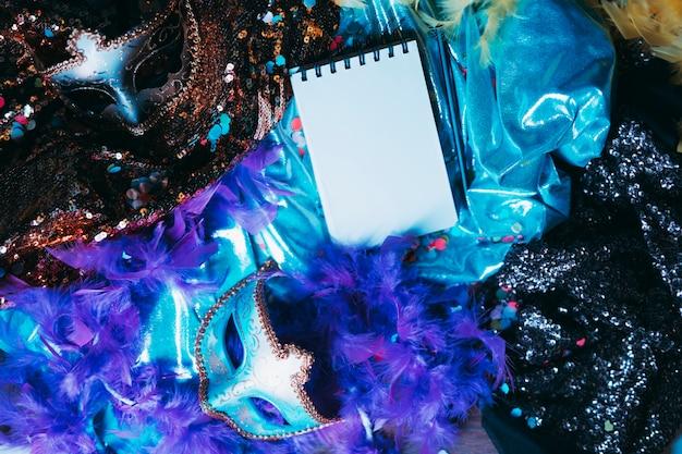 Bloc de notas en espiral sobre elegantes accesorios de carnaval.