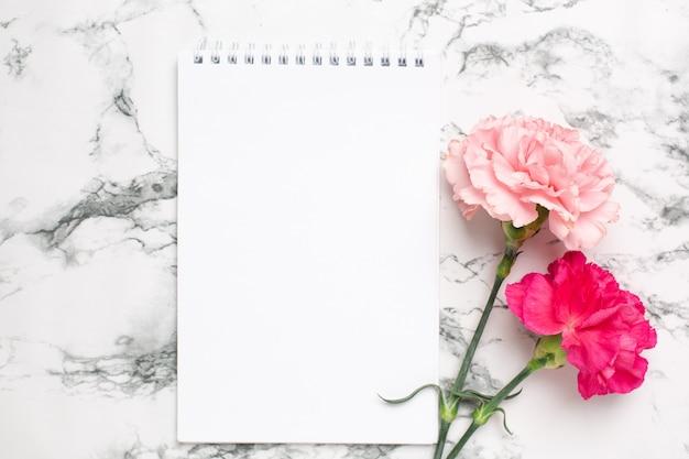 Bloc de notas y flor de clavel rosa sobre mármol