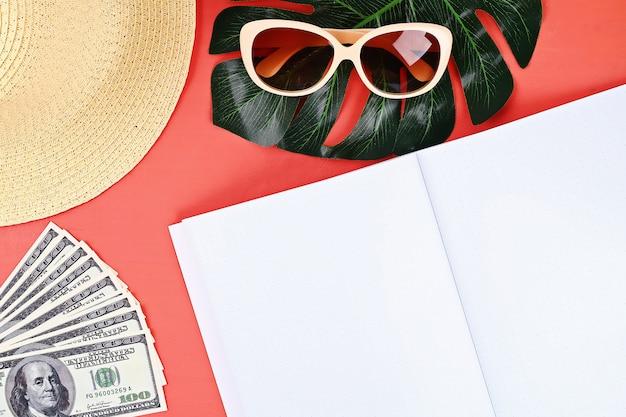 Bloc de notas de fondo coral, gafas de sol, sombrero, dinero.