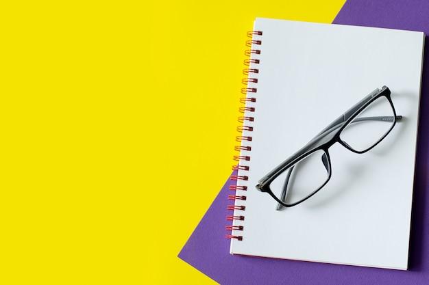 Bloc de notas y gafas sobre un fondo multicolor con copyspace