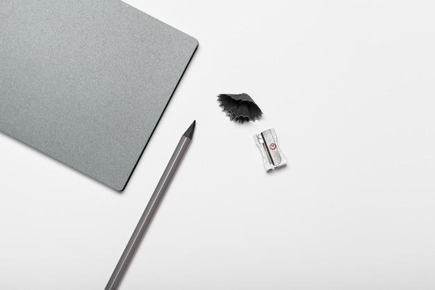 Bloc de notas gris y lápiz en la vista superior de la mesa de trabajo