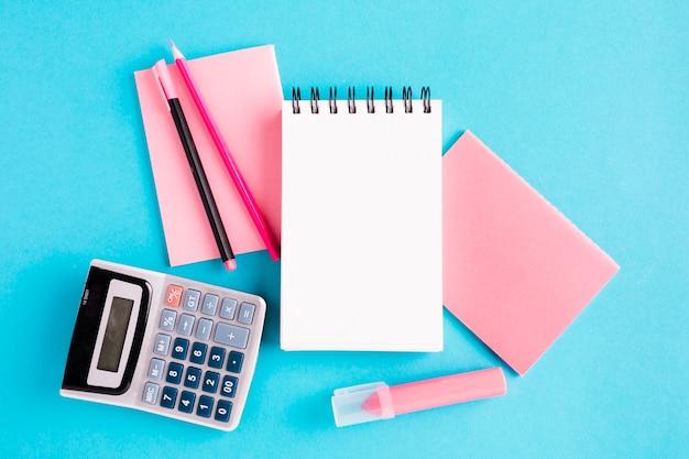 Bloc de notas y herramientas de oficina en superficie azul.