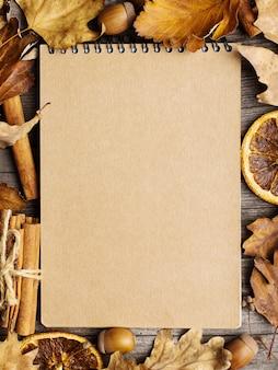 Bloc de notas, hojas, naranja seca, canela y bellotas en la vieja mesa de madera