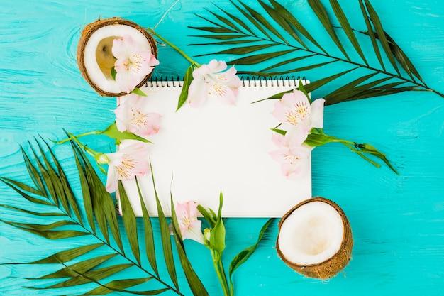 Bloc de notas entre hojas de planta con cocos frescos y flores.