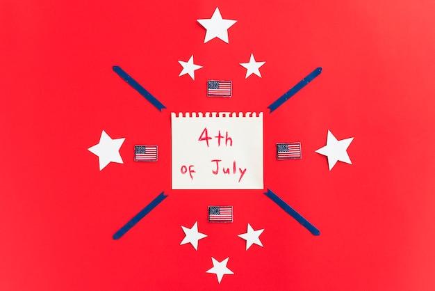 Bloc de notas con inscripción el 4 de julio y diseño con estrellas en superficie roja.