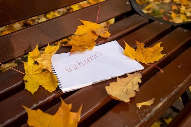 Bloc de notas con inscripción otoño se encuentra en un banco del parque en hojas de otoño en el sol brillando