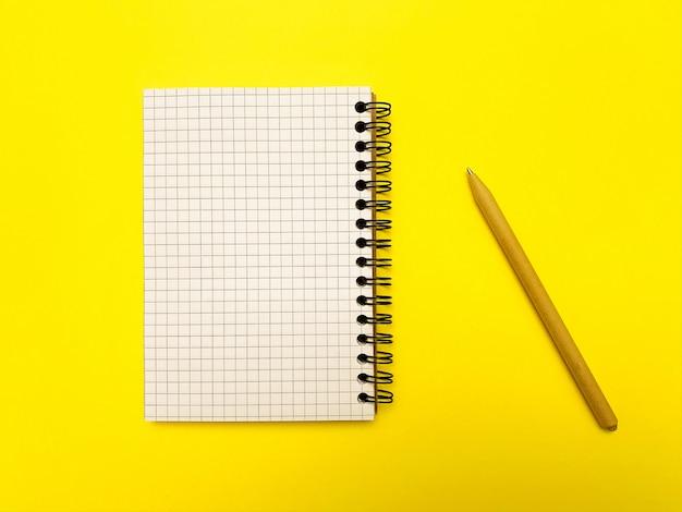 Bloc de notas y lápiz para escribir sobre una superficie amarilla