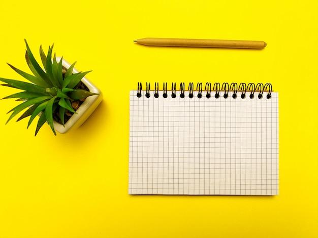 Bloc de notas, lápiz y planta para escribir sobre una superficie amarilla