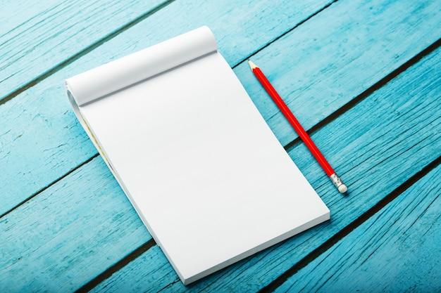 Bloc de notas con lápiz rojo sobre un fondo de mesa de madera azul, para educación, escribir objetivos y hechos