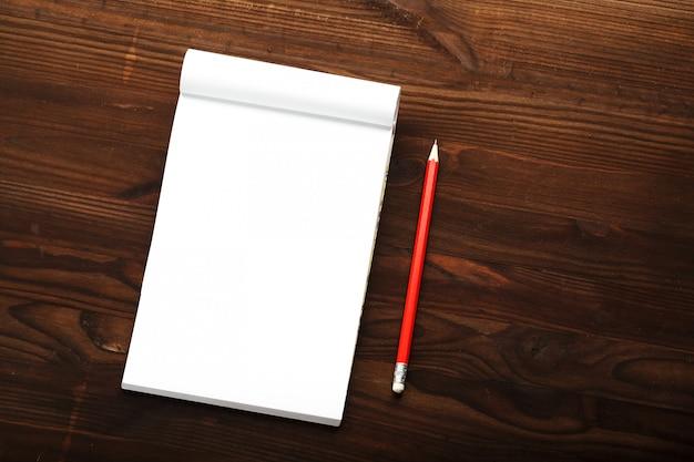 Bloc de notas con lápiz rojo sobre un fondo de mesa de madera marrón, para educación, escribir objetivos y hechos
