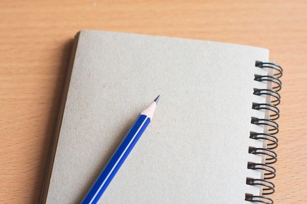 Bloc de notas con lápiz sobre fondo de tablero de madera. uso de papel tapiz para educación, foto de negocios. tome nota del producto para el libro con papel y concepto, objeto o espacio de la copia.