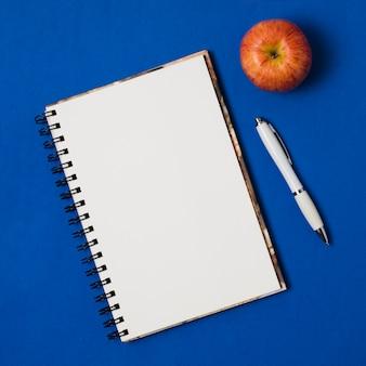 Bloc de notas de maqueta con manzana sobre fondo azul oscuro