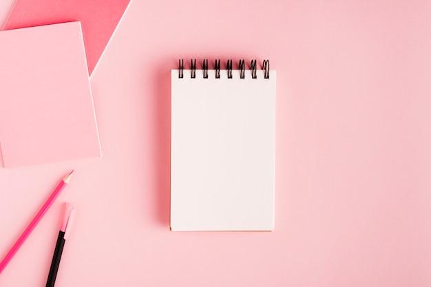 Bloc de notas y material de oficina en superficie de color.