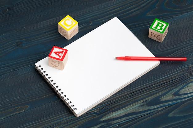 Bloc de notas en mesa de madera y bloques de madera del alfabeto