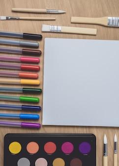 Bloc de notas con muchos lápices de colores y pincel sobre mesa de madera marrón