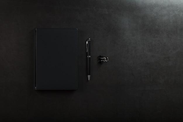 Bloc de notas negro con un bolígrafo negro sobre fondo negro. vista superior, concepto minimalista. espacio libre.