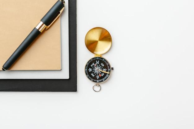 Bloc de notas negro para notas náuticas y brújula dorada sobre un fondo blanco de mesa