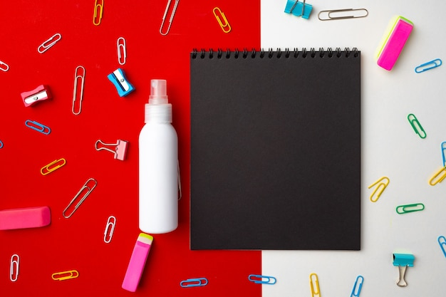 Bloc de notas negro rodeado con vista superior de clips de papel