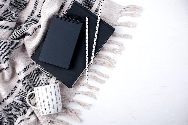 Bloc de notas negro, taza y cuadros sobre fondo blanco.