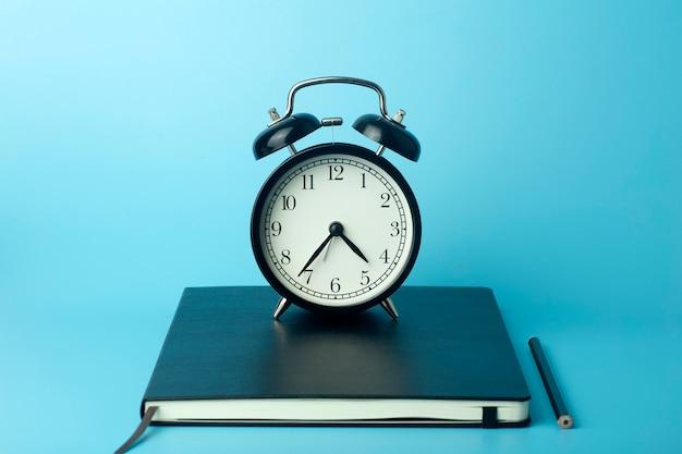 Bloc de notas para notas adhesivas en el escritorio con reloj despertador. concepto de escritorio, administración y sincronización de office.