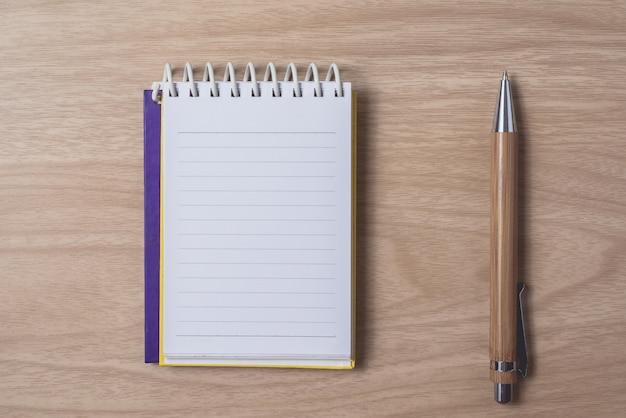 Bloc de notas o cuaderno con bolígrafo en la mesa de madera marrón.uso para educación, fondo de negocios