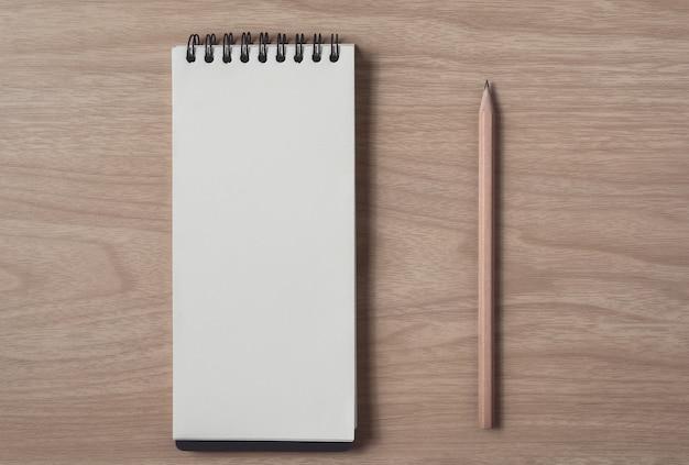 Bloc de notas o cuaderno con lápiz sobre tabla de madera marrón.uso para educación, negocios