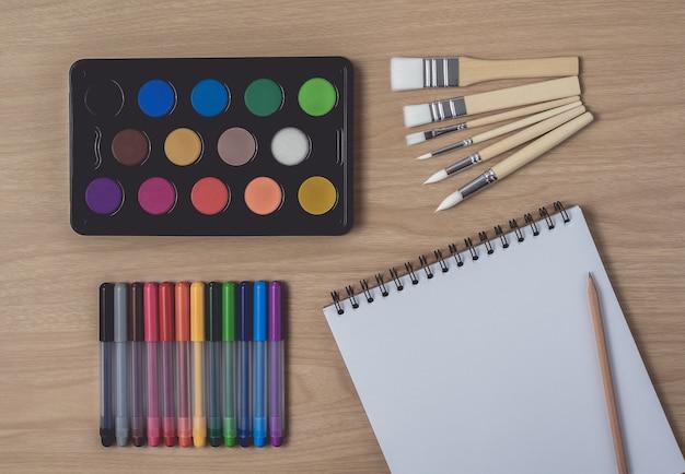 Bloc de notas o cuaderno con muchos bolígrafos de colores, pincel y paleta de acuarela sobre mesa de madera marrón.uso para artes y educación