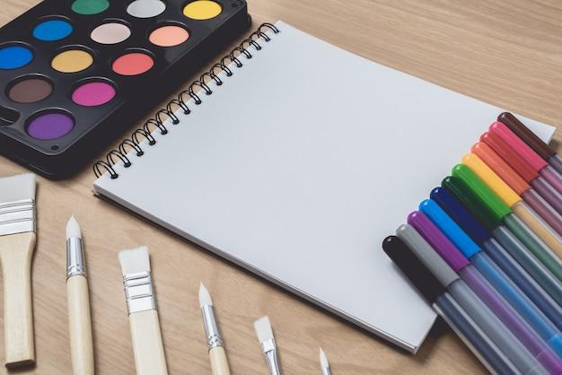 Bloc de notas o cuaderno con muchos bolígrafos de colores, pincel y paleta de acuarela sobre mesa de madera marrón.uso para fondo de arte y educación