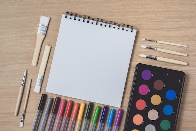 Bloc de notas o cuaderno con muchos bolígrafos de colores, pincel y paleta de acuarela sobre una mesa de madera marrón.