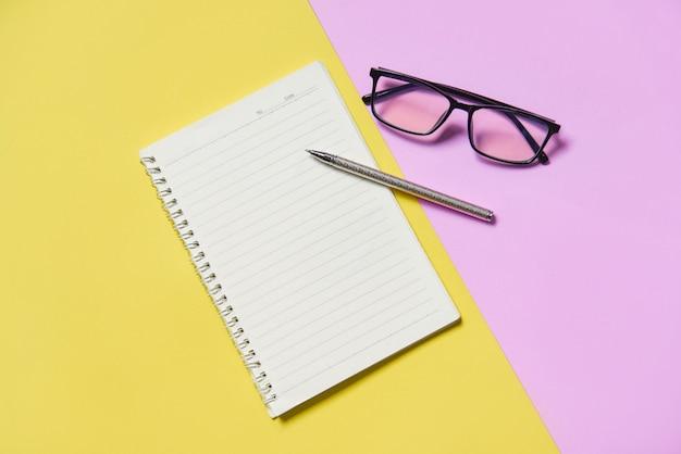 Bloc de notas o papel de cuaderno con bolígrafo y gafas en rosa amarillo