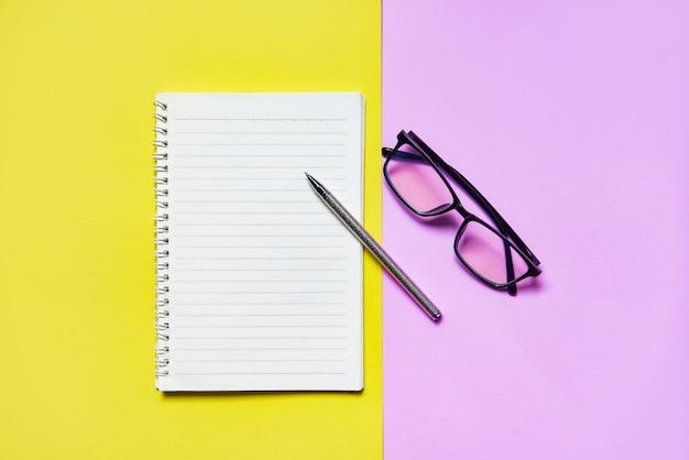 Bloc de notas o papel de cuaderno con bolígrafo y lentes en amarillo rosado para educación y concepto de negocio