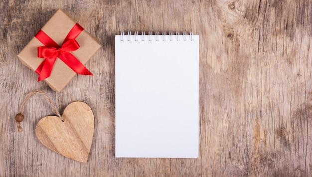 Bloc de notas con página en blanco, un corazón de madera y caja de regalo con un lazo rojo.