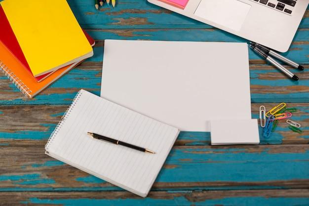 Bloc de notas, página en blanco, diarios, bolígrafos, lápices de colores, laptop y alfileres de papel
