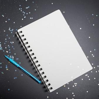 Bloc de notas página en blanco rodeada de confeti