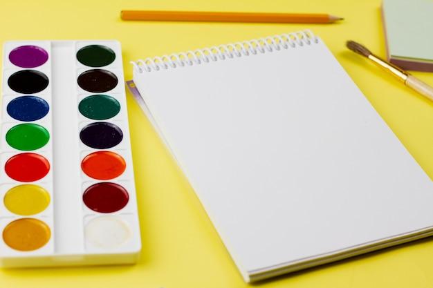 Bloc de notas con pintura sobre un fondo amarillo.