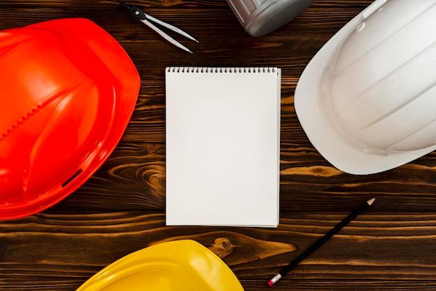 Bloc de notas plano con cascos de construcción.