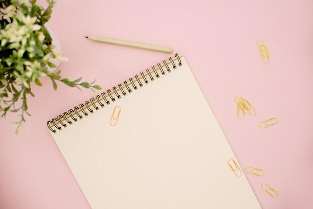 Bloc de notas y una planta verde sobre fondo rosa con espacio de copia