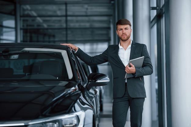 Con bloc de notas plateado en la mano. empresario barbudo con estilo moderno en el salón del automóvil