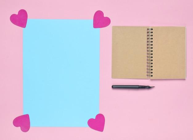 Bloc de notas con pluma, espacio de copia azul con corazones decorativos en una superficie de color rosa pastel. vista superior. minimalismo