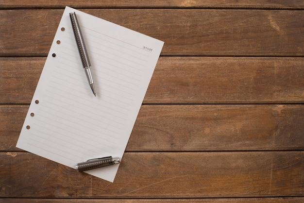 Bloc de notas con pluma en la mesa de madera de la oficina.