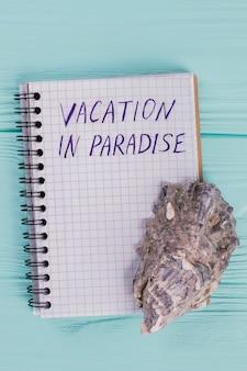 Bloc de notas de primer plano con vacaciones de palabras en el paraíso y concha de mar tropical en el escritorio azul. piso de vacaciones sentar.